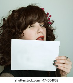Young woman with an empty white card. Wink eye.