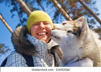 young woman emracing sled dogs