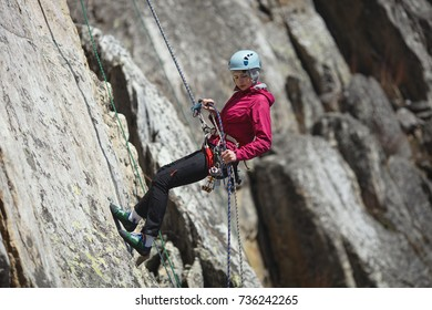 Young woman is engaged in rock climbing in the mountains. Sport climbing.