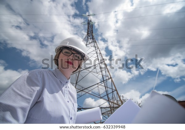 young woman engeneer with electicity grid plans and power lines in background