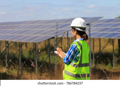 young woman engineer checking solar panel at solar power plant