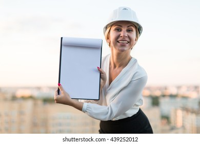 Young woman engineer in a helmet with a folder is a folder on the background of the city