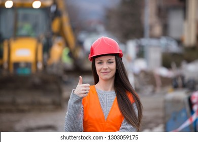 Young woman engineer with helmet showing thumb up as ok sign in front of excavator at construction site