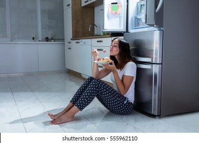 Young Woman Enjoy Eating Sweet Food While Sitting On Floor In Kitchen