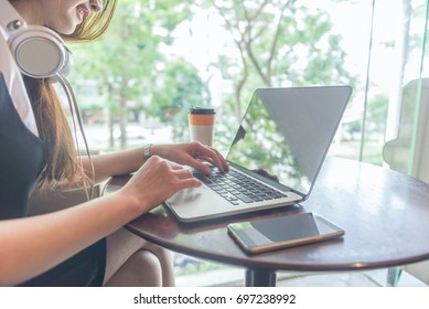 Young woman enjoy her day with coffee, music and surfing the Internet