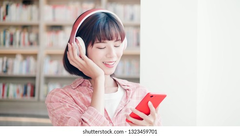 young woman enjoy music and use smart phone in the library