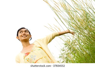 Young woman enjoy nature with her hand touching the grass