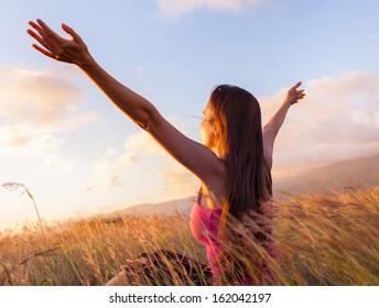 Young woman enjoy sunshine in wheat field