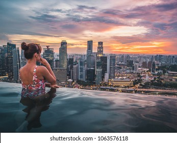Young woman enjoying amazing sunset view from infinity-pool on the roof of skyscraper in Singapore. Big city urban skyline.