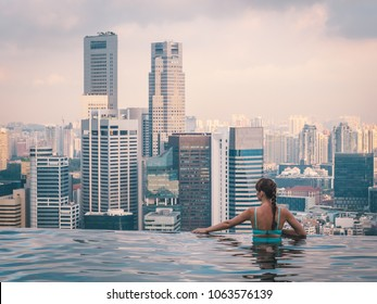 Young woman enjoying amazing view from infinity-pool on the roof of skyscraper in Singapore. Big city urban skyline.