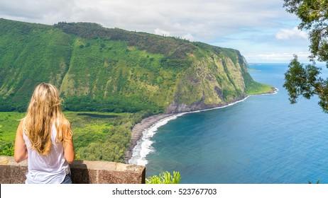 Young woman enjoying the amazing view in Waipio Valley, Big Island, Hawaii, Usa