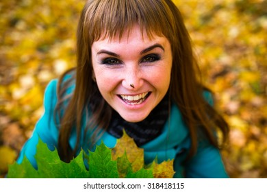 Young woman enjoying in autumn park playing with leaves, snail on the nose