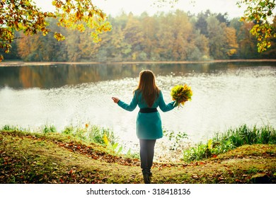 Young woman enjoying in autumn park playing with leaves