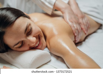 Young woman enjoying a back massage in a spa center.
