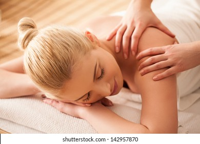 Young woman enjoying a back massage at a spa centre.