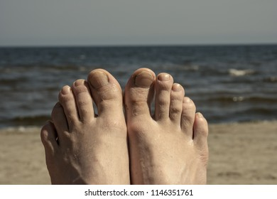 young woman enjoying beach with feet against the sea