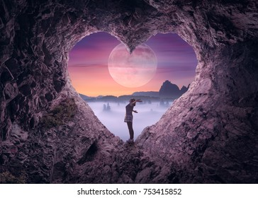 Young woman enjoying in beautiful night mountain nature, celebrating freedom and rising her arms while standing toward the big moon. Valentines day concept.