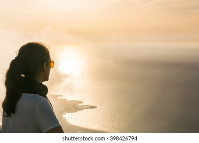 Young woman enjoying the beautiful sunset from the viewpoint