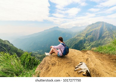 Young woman enjoying breathtaking views over mountains and tea plantations from Little Adams peak in Ella Sri Lanka