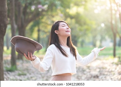 Young woman enjoying with cherry blossom garden in Spring day
