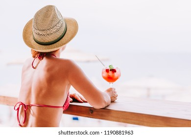 Young woman enjoying cocktail in a beach bar