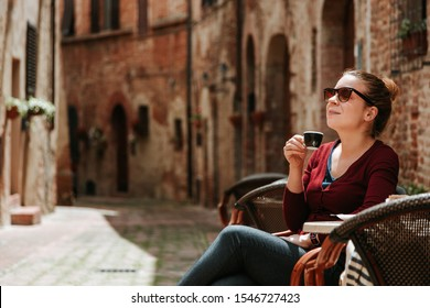 Young woman enjoying coffee in in a cafe in medieval town in Tuscany, Italy