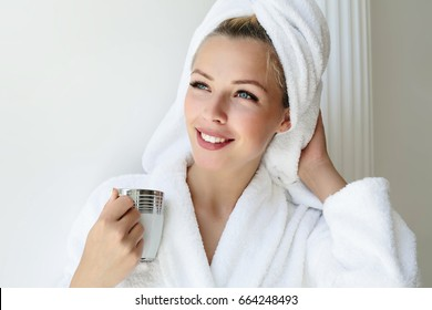 Young woman enjoying  coffee at home.Morning coffee is my daily routine.Soft photo of fresh young woman in white tender bathrobe drinking tea.Cheerful  young woman  smiling and looking at the window