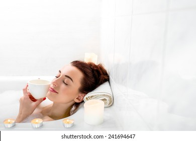 Young woman enjoying coffee while lying in the bath with foam and candles. General plan with space for text