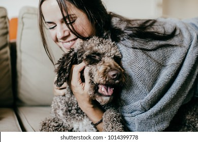Young woman enjoying a cup of coffee at home, wearing comfortable clothes and playing with her dog. Lifestyle photography