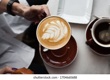 Young woman enjoying a cup of coffee, view from above