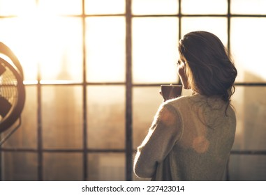 Young woman enjoying cup of coffee in loft apartment. rear view