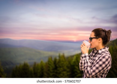 Young woman is enjoying cup of coffee outside with beautiful view of mountains and woods during a sunset/sunrise. Dark hair girl drinking cup of tea on a terace.