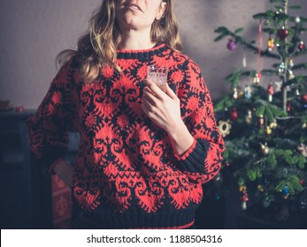 A young woman is enjoying a drink by the christmas tree