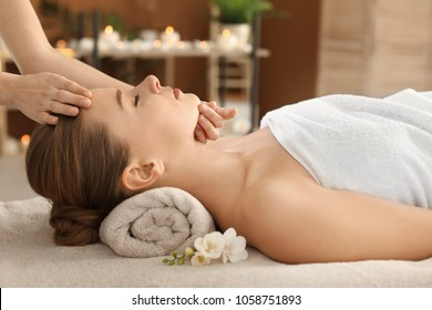 Young woman enjoying face massage in spa salon