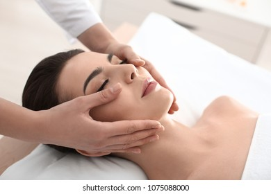 Young woman enjoying facial massage in spa salon