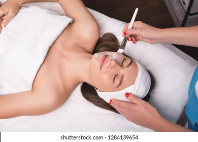 Young woman is enjoying facial procedure at beauty salon. Girl is lying in spa and getting clay mask with pleasure