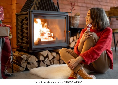 Young woman enjoying fire while sitting with Christmas candy by the fireplace during winter holidays. Warmth and coziness in winter concept