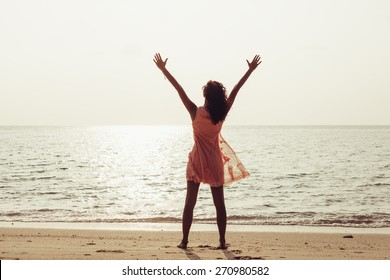 Young woman enjoying freedom feeling happy at beach at sunset. Beautiful serene relaxing girl in pure happiness and elated enjoyment with arms raised outstretched up. Latin Caucasian female model.