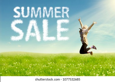 Young woman enjoying freedom jumping on field. Summer sale concept.