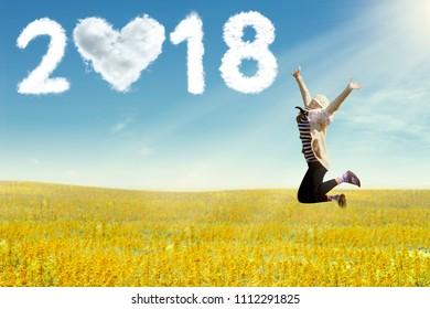 Young woman enjoying freedom jumping on field. New year 2018 concept.