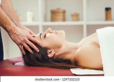 Young woman is enjoying head massage on spa treatment.