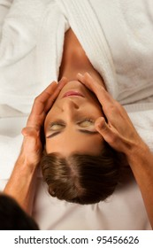 Young woman enjoying head massage or cosmetic treatment in Spa