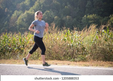 young woman enjoying in a healthy lifestyle while jogging along a country road, exercise and fitness concept