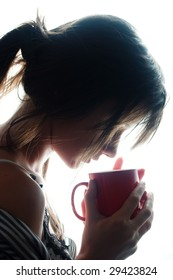 Young woman enjoying her coffee near the window