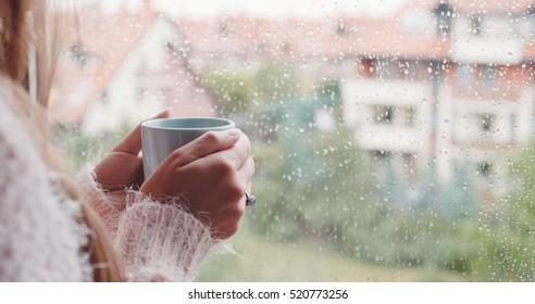Junge Frauen, die ihren Morgenkaffee oder Tee genießen, mit Blick auf das Regenfenster. Schönes romantisches, unerkennbares Mädchen, das heiße Getränke zu Hause trinkt. Regentag-Stimmung.