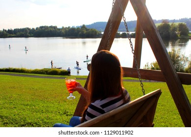 Young woman enjoying her sundowner drink on a wooden swing watching people practicing SUP