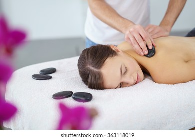 Young woman enjoying a hot rock massage in a spa salon as heated basalt stones are placed on her muscles prior to commencing the massage