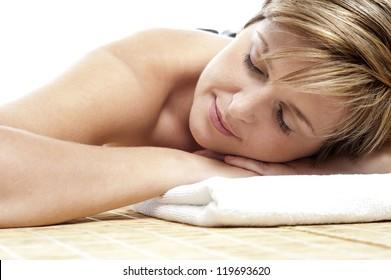 Young woman enjoying hot stone spa treatment at salon