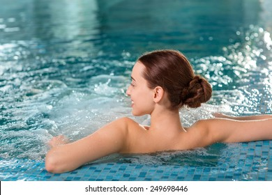 Young woman enjoying jacuzzi in the swimming pool at the hotel spa