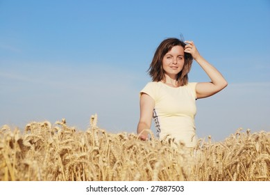 Young woman enjoying life in golden wheat field before harvest